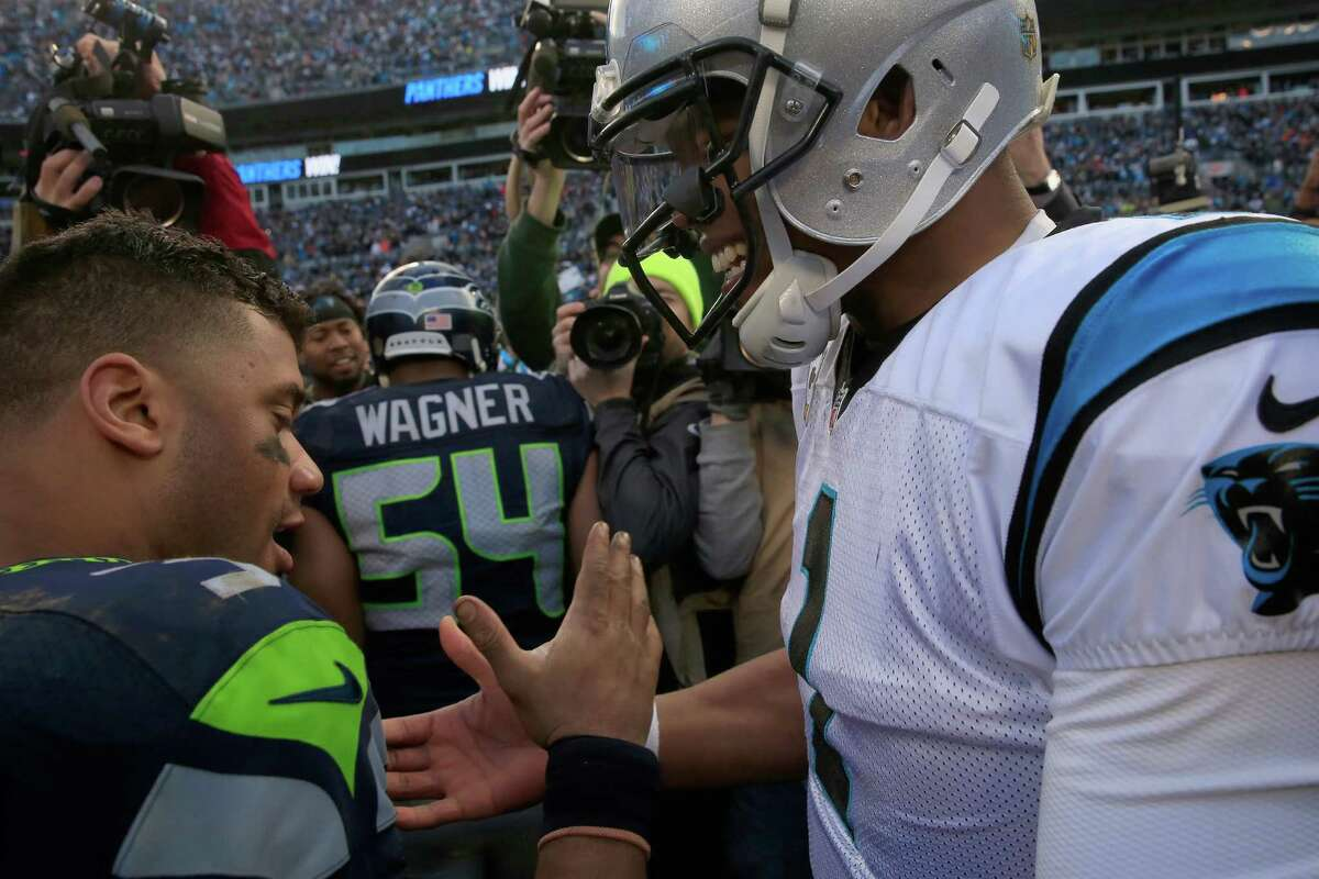 CHARLOTTE, NC - JANUARY 17: Cam Newton #1 of the Carolina Panthers meets Russell Wilson #3 of the Seattle Seahawks on the field after the NFC Divisional Playoff Game at Bank of America Stadium on January 17, 2016 in Charlotte, North Carolina.