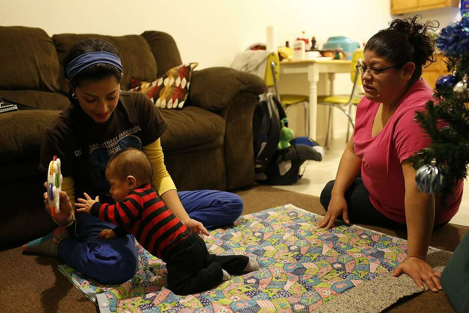 Elaine Boch, an early childhood intervention specialist, works with Chance Miracle Rodriguez, 11 months, as his mother, Anita Solis, right, watches at their home in Seguin on Friday, Dec. 18, 2015. Photo: Lisa Krantz, SAN ANTONIO EXPRESS-NEWS