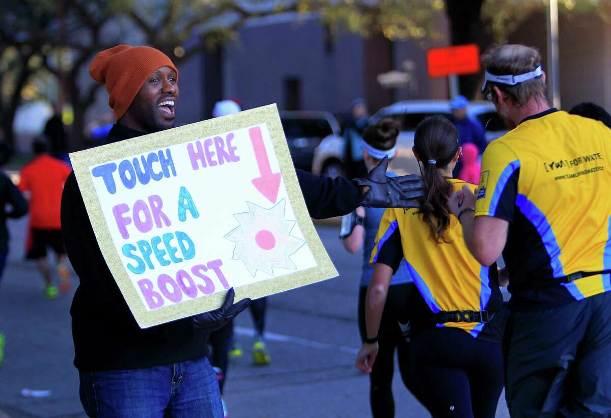 """Clarence Stevens offers a """"speed boost"""" to half-marathoners near the Museum of Fine Arts, Houston."""