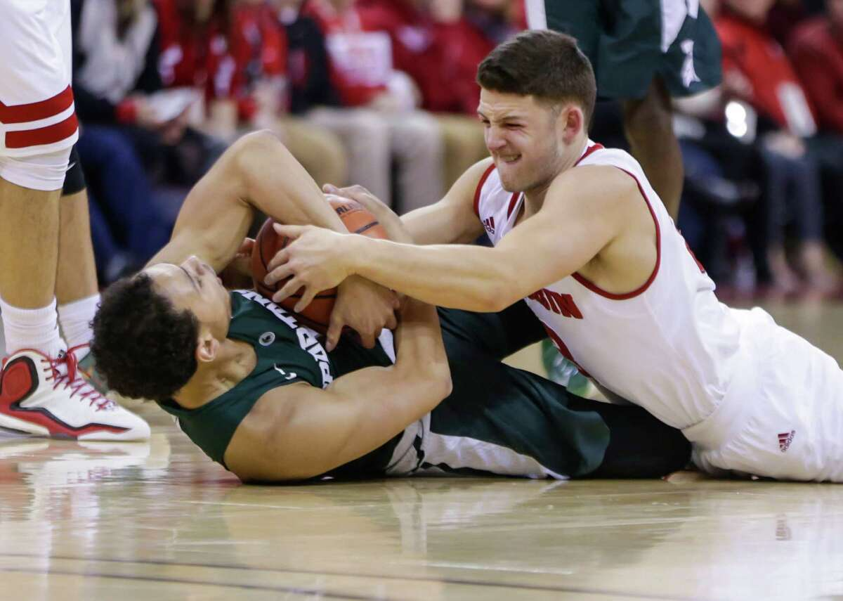 Michigan State's Bryn Forbes, left, and Wisconsin's Zak Showalter, right, battle for a loose ball during an NCAA college basketball game Sunday, Jan. 17, 2016, in Madison, Wis. Wisconsin upset Michigan State 77-76. (AP Photo/Andy Manis) ORG XMIT: WIAM118
