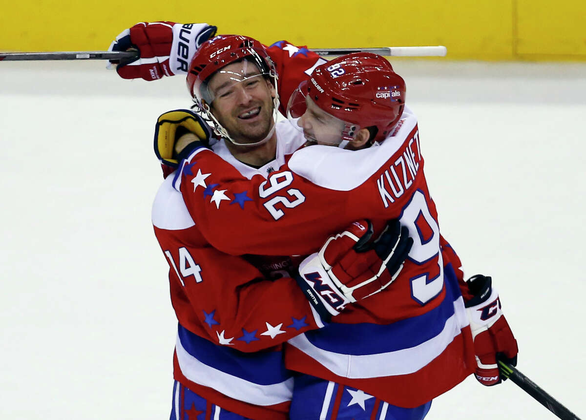 Washington Capitals right wing Justin Williams (14) celebrates his second goal in the third period of an NHL hockey game with center Evgeny Kuznetsov (92), form Russia, Sunday, Jan. 17, 2016, in Washington. Williams scored the empty net goal for a hat trick. The Capitals won 5-2. (AP Photo/Alex Brandon) ORG XMIT: VZN112