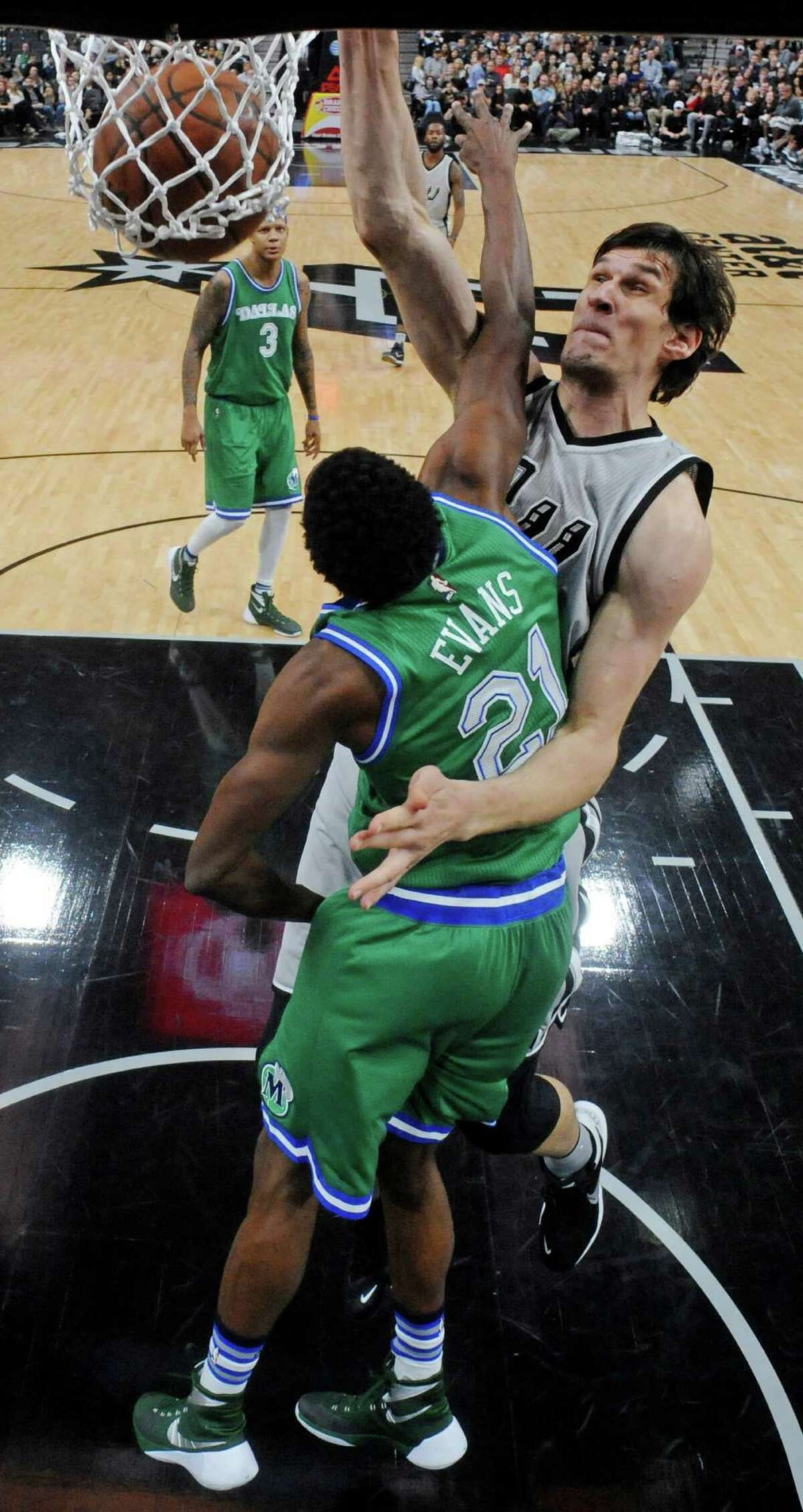 Spurs' Boban Marjanovic dunks over Dallas Mavericks' Jeremy Evans during second half action on Jan. 17, 2016 at the AT&T Center. Marjanovic received a technical foul for taunting after the play.