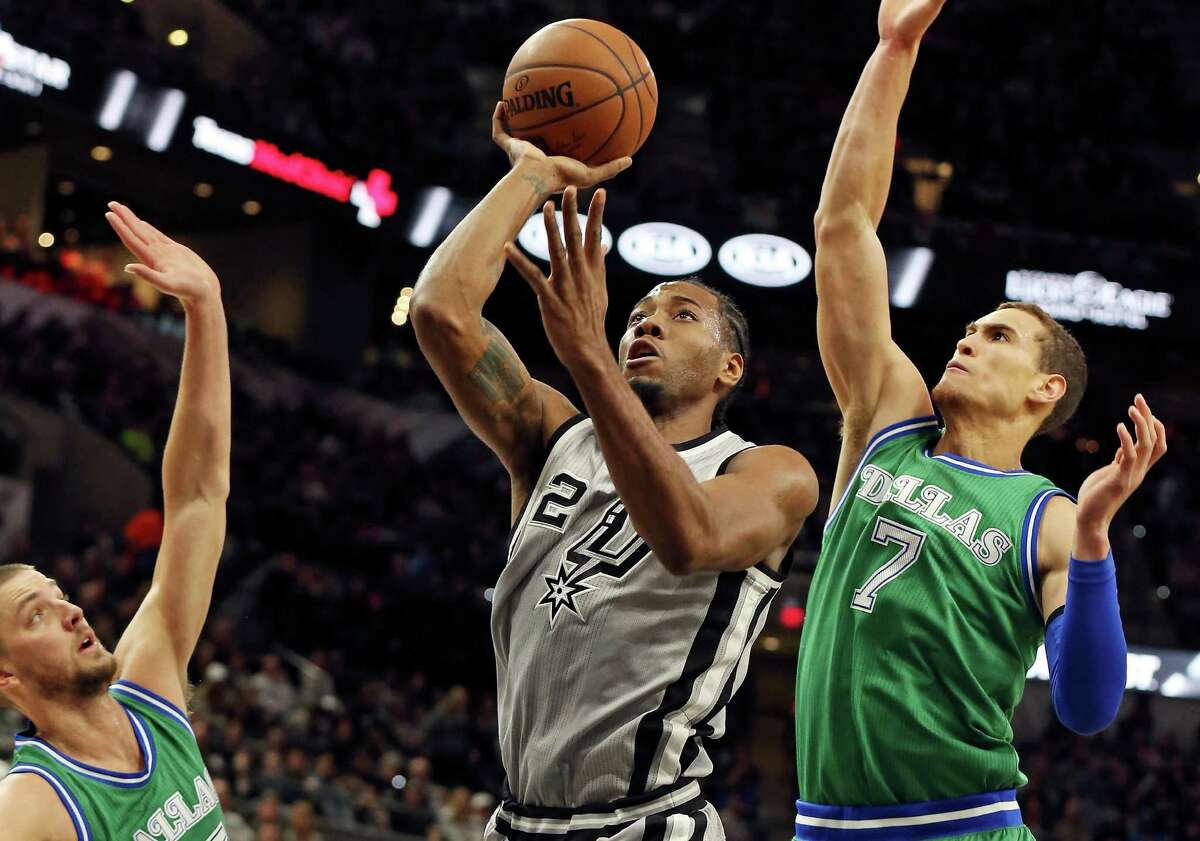 Spurs' Kawhi Leonard shoots between Dallas Mavericks' Chandler Parsons (left) and Dwight Powell during first half action on Jan. 17, 2016 at the AT&T Center.