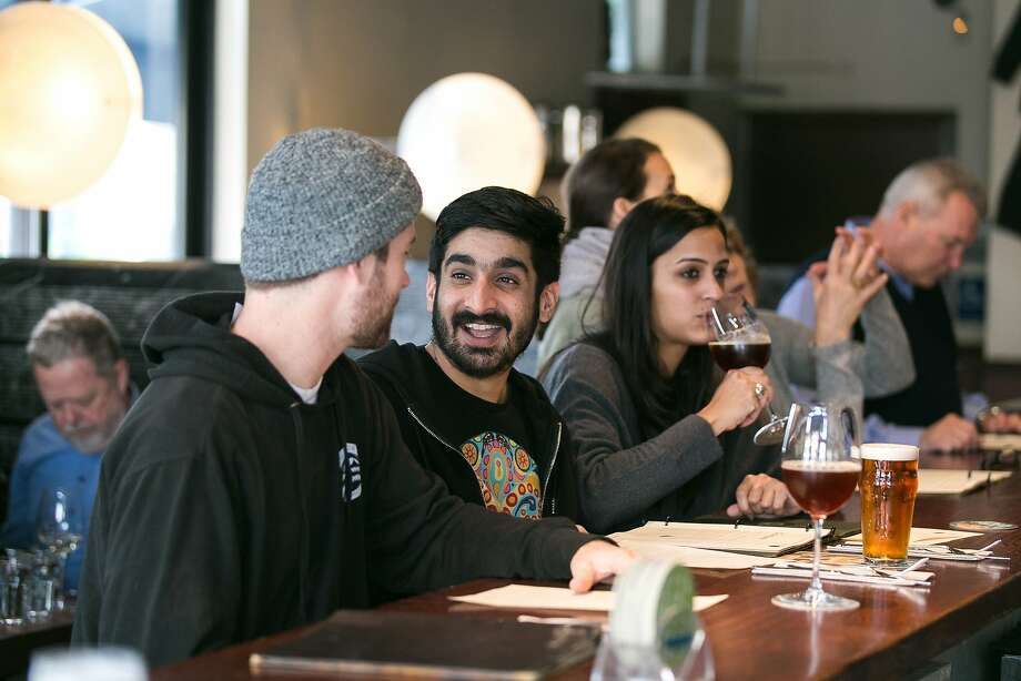 Jesjit Birak (center) has a beer with friends Tim Linden (left) and Rhia Bakshi (right) at the bar at Monk's Kettle in S.F. Photo: Jen Fedrizzi, Special To The Chronicle