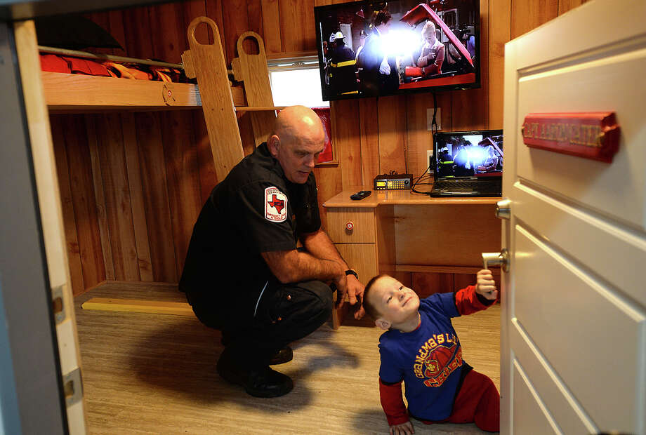 Six-year-old Aaron Cater gets a tour of his new fire station playhouse, complete with captain's nameplate, and vehicle from Port Arthur Fire Department Captain Gerrit Achord during a surprise unveiling of the structure at his home i Groves Saturday. The department built the home for Aaron, who was born with spin bifida, in conjunction with support from CASA. Aaron decided one year ago that he wanted to be a firefighter and frequently visits the Port Arthur fire department.  Photo taken Saturday, January 16, 2016  Kim Brent/The Enterprise Photo: Kim Brent / Beaumont Enterprise
