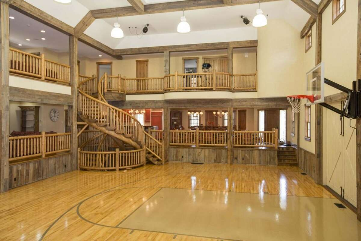 """A seven-bedroom party house in New Canaan with an asking price of $15,000,000 has been on the market since the end of January. The Home Builders & Remodelers Association of Connecticut winning property features a separate """"sports"""" barn equipped with a golf simulator, basketball court and other entertainment accessories. Read more."""