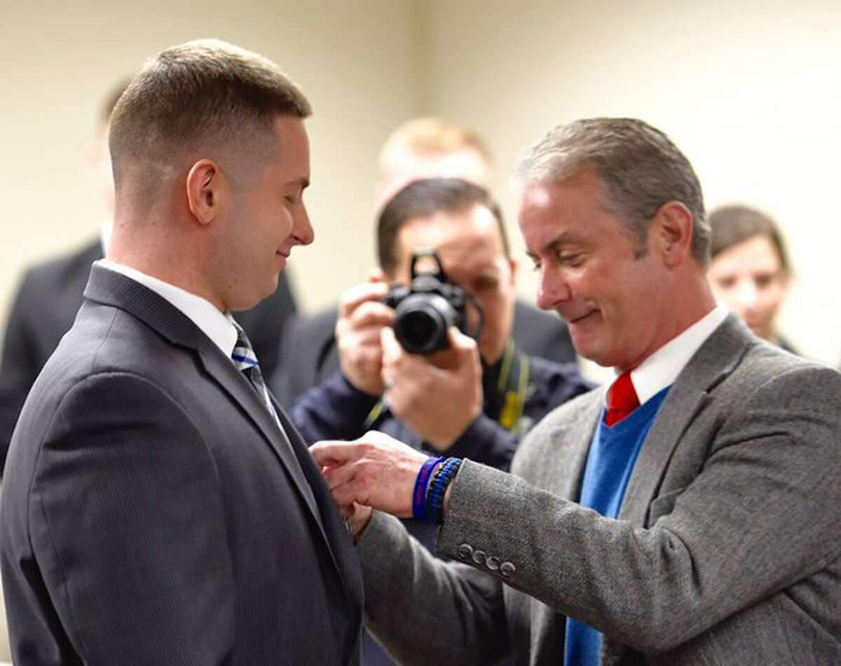 Nick Colaneri receives his badge from his dad Det. Sgt. Tim Colaneri after being sworn as a Troy police officer. (Skip Dickstein / Times Union)