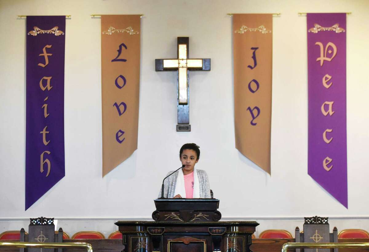 """Nalani Zhuta-Medley, 12, recites her speech during the Fourth Annual the Rev. Dr. Martin Luther King Jr. Oratorical Contest at First Baptist Church in Greenwich, Conn. Monday, Jan. 18, 2016. Participants responded to Dr. King's statement """"A riot is the language of the unheard,"""" relating that quote to the context of today's society."""