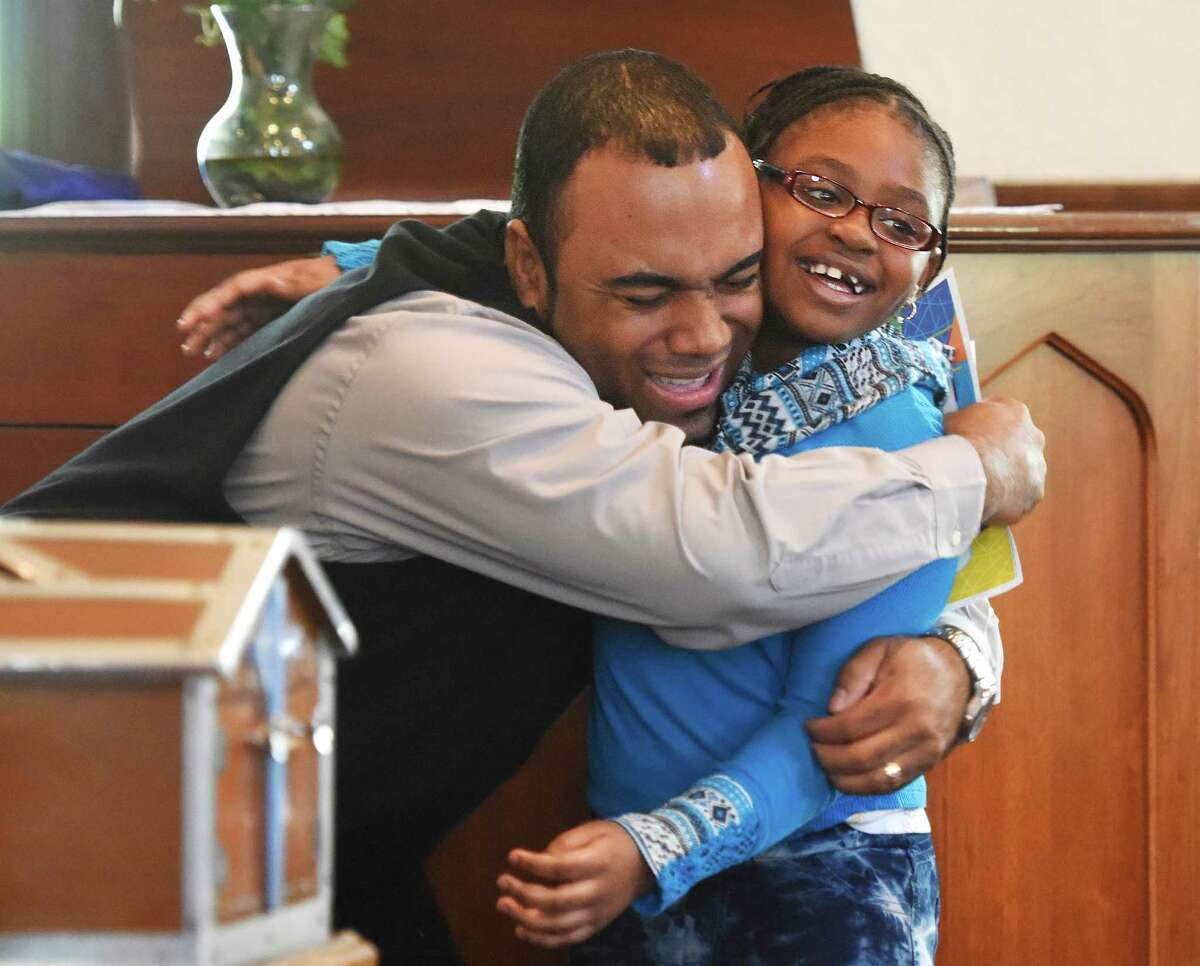 """Youth minister Dwain Newell hugs Jatana Wright, 8, after awarding her for her speech during the Fourth Annual the Rev. Dr. Martin Luther King Jr. Oratorical Contest at First Baptist Church in Greenwich, Conn. Monday, Jan. 18, 2016. Participants responded to Dr. King's statement """"A riot is the language of the unheard,"""" relating that quote to the context of today's society."""