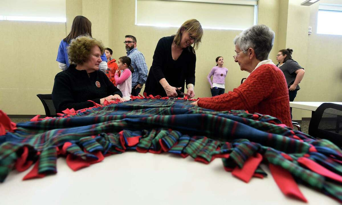 Marry Ellen Roger, left, Mary Beth Hassett-Murphy, center and Dianne Halton work on a fleece blanket for the Saratoga CAPTAIN program at the Clifton Park-Halfmoon Library in observance of Martin Luther King day Jan. 18, 2016 in Clifton Park, N.Y. (Skip Dickstein/Times Union)