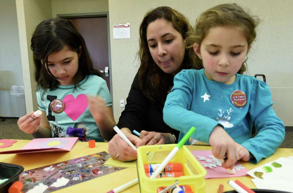 The Lape family works on greeting cards at the Clifton Park-Halfmoon Library in observance of Martin Luther King day Jan. 18, 2016 in Clifton Park, N.Y. The Lape's are from left to right; Isabella, 8, left; mom, Maribel and Ceci age 4 and all are from Clifton Park. (Skip Dickstein/Times Union)
