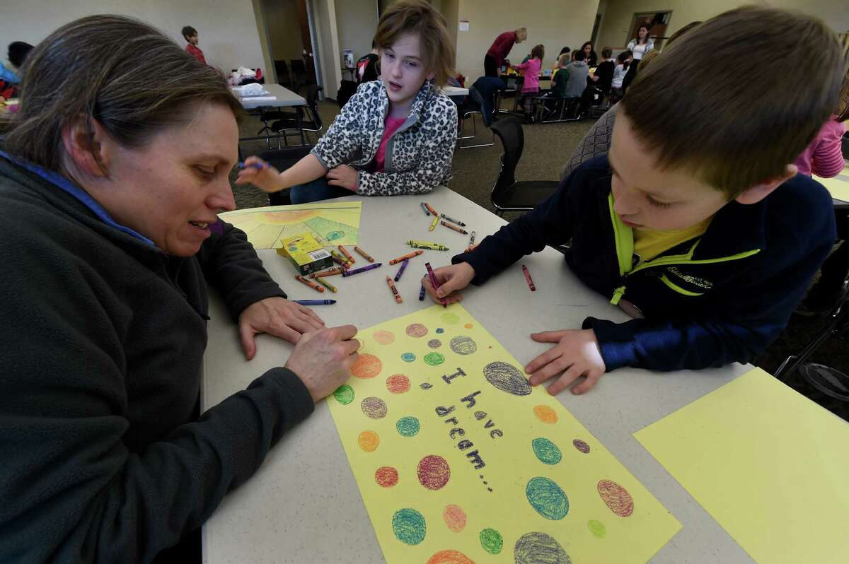 Mom, Denise Donnell, left works on placemats with her children Alison Szczesny, center, 10 and Maximilian, 9 at the Clifton Park-Halfmoon Library in observance of Martin Luther King day Jan. 18, 2016 in Clifton Park, N.Y. The place mats will be given to a charity as part of the MLK program at the Library. (Skip Dickstein/Times Union)