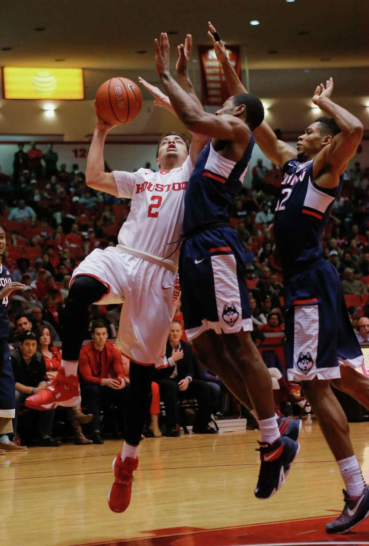 Houston guard Rob Gray Jr., left, drives to the basket as Connecticut guard Rodney Purvis, center, and forward Shonn Miller, right, defends during the second half of an NCAA college basketball game Sunday, Jan. 17, 2016 in Houston. Connecticut won 69-57. (AP Photo/Bob Levey)