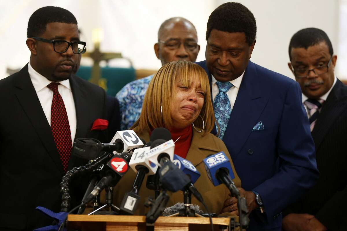 Gwen Woods (center), the mother of Mario Woods, speaks through tears while being comforted by attorney John Burris (right) during a news conference at Allen Chapel in San Francisco, California, on Monday, Jan. 18, 2016.