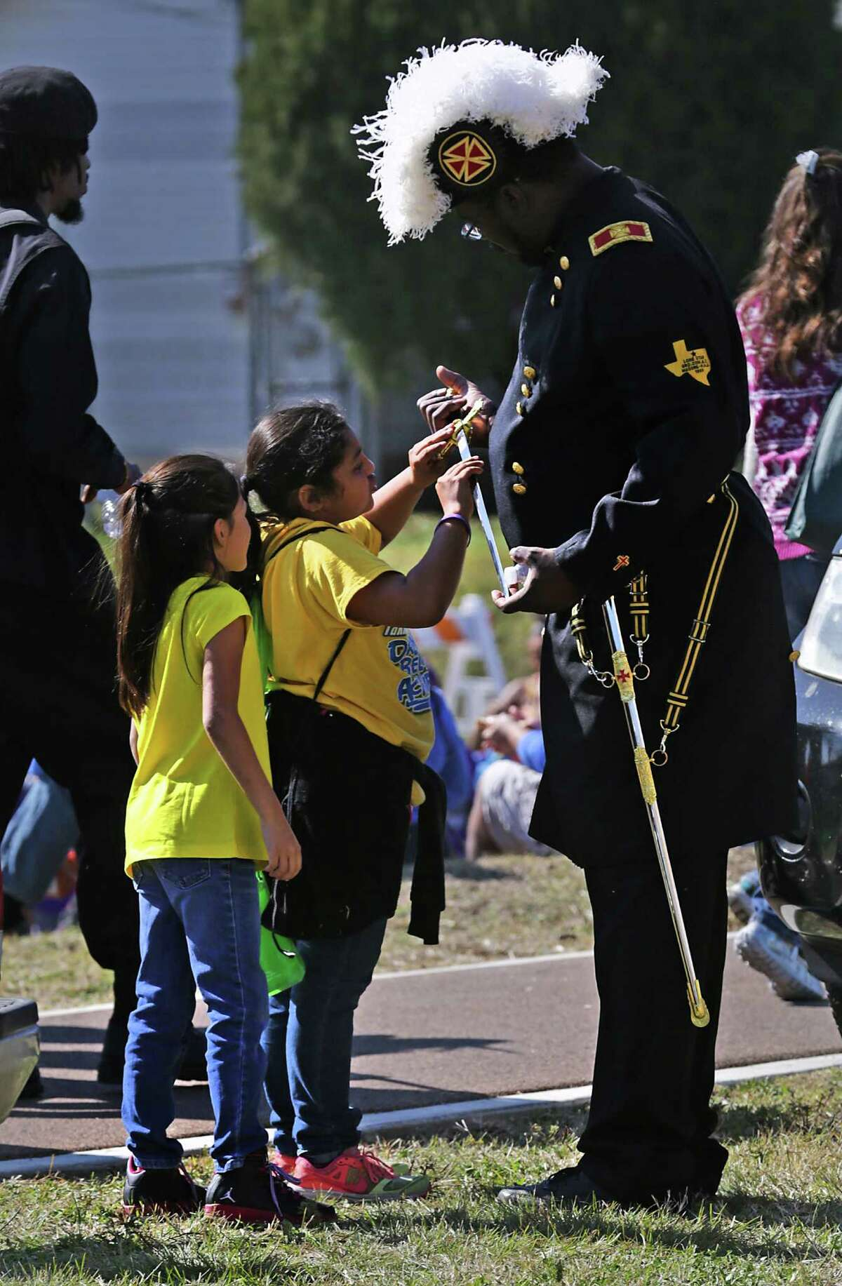 Clary Glover, right, a member of the Knights Templar Alamo Commandry #7 gives Leahlani Huerta, 8, center, and Monica Aguuilar, 9, a close look at his ceremonial saber at the end of the 2016 Martin Luther King Jr March before the Commemorative Program at Pittmann-Sullivan Park on Monday, Jan. 18, 2016.