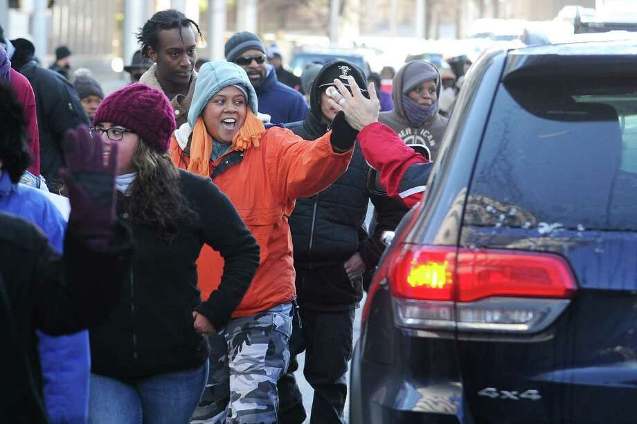 Krystal Collins high-fives a supportively honking motorist at the corner of Atlantic St. and Tresser Blvd. during Stamford's annual Martin Luther King, Jr. march, which wove through downtown Stamford on Jan. 18, 2016. Photo: Michael Cummo / Hearst Connecticut Media / Stamford Advocate