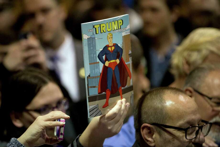 A woman holds up a Donald Trump coloring book, depicting the Republican presidential candidate as Superman, at a rally in Cedar Falls, Iowa. Far from Superman, a reader thinks Trump is a tool for terrorists. Photo: Jae C. Hong /Associated Press / AP