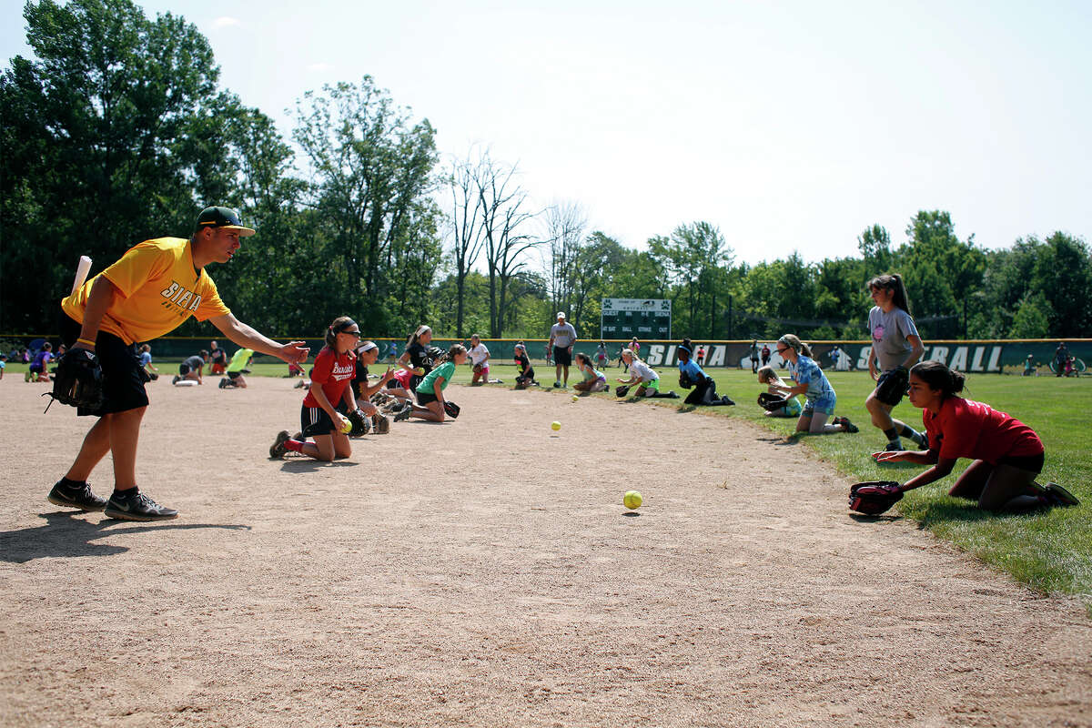 Alex Jurczynski of Siena Saints baseball helps train young softball players during an athletics camp hosted by Siena College on Monday, July 21, 2014 at Siena College in Loudonville, N.Y. (Tom Brenner/ Special to the Times Union)