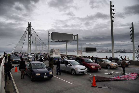 Protesters momentarily shut down lanes of the Bay Bridge after chaining themselves to cars across all five lanes.