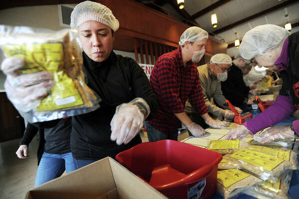 From left; Cristina Martin and husband Dru Martin, of Fairfield, volunteers for Operation Hope, help assemble and package over fourteen thousand meals of fortified macaroni and cheese at Grace Lutheran Church in Stratford, Conn. on Monday, January 18, 2016. Food boxes are being distributed to Sterling House in Stratford, Operation Hope in Fairfield, and the Bridgeport Rescue Mission.