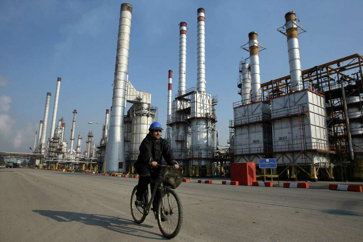 An Iranian oil worker rides his bicycle at the Tehran's oil refinery south of Tehran, Iran. Iran expanded production by 80,000 barrels a day to 2.99 million in January.
