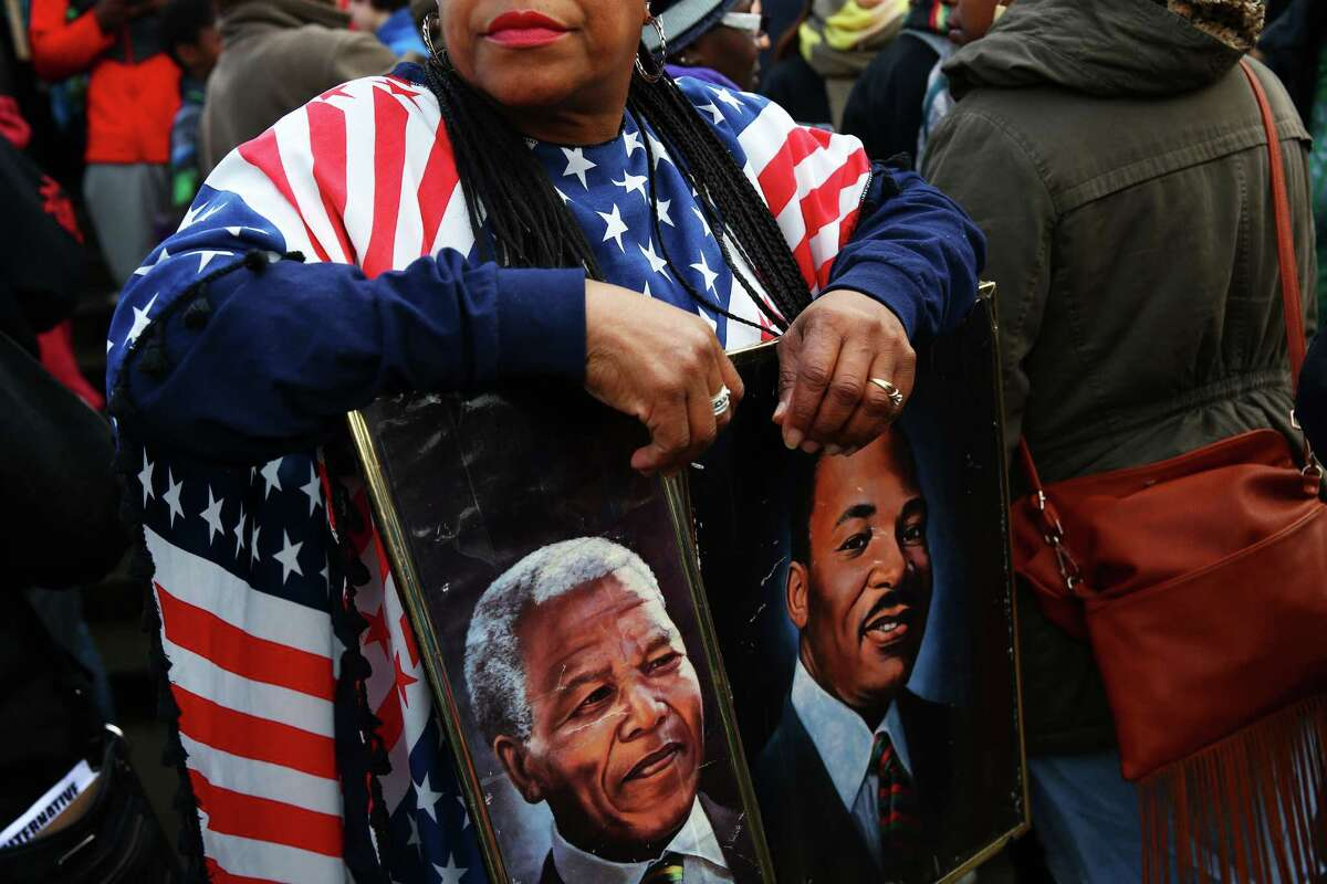 Fai Mathews displays paintings of Martin Luther King Jr. and Nelson Mandela during the 34th Annual Martin Luther King Jr. Day Celebration March, Monday, Jan. 18, 2016. Several thousand people marched from Garfield High School to the federal building downtown.