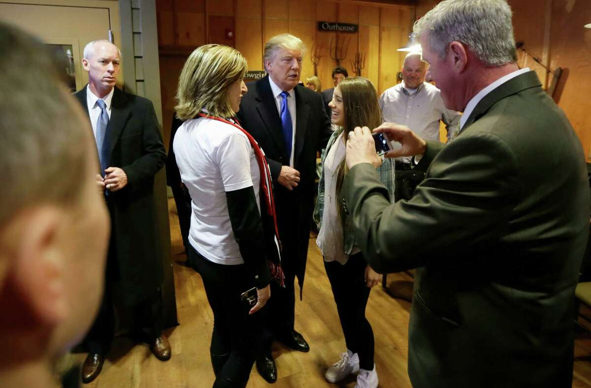 Republican presidential candidate Donald Trump talks with supporters before meeting with volunteers at the local Pizza Ranch restaurant, Friday, Jan. 15, 2016, in Waukee, Iowa. (AP Photo/Charlie Neibergall) ORG XMIT: IACN104