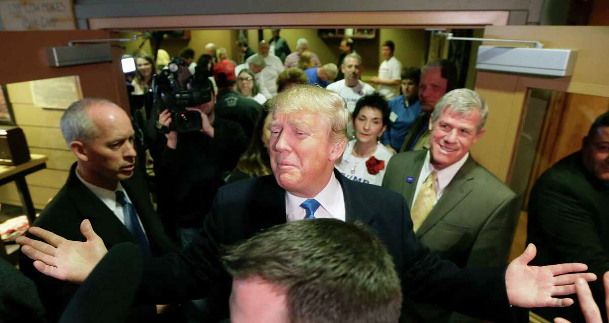 Republican presidential candidate Donald Trump reacts to supporters after meeting with volunteers at the local Pizza Ranch restaurant, Friday, Jan. 15, 2016, in Waukee, Iowa. (AP Photo/Charlie Neibergall) ORG XMIT: IACN102