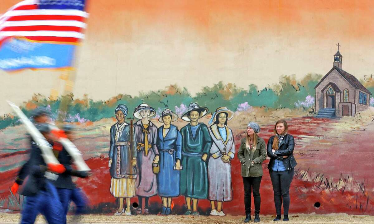 Ashley France, left, and Lauren Beeler watch a color guard in the Rev. Martin Luther King Jr. parade in downtown Oklahoma City, Monday, Jan. 18, 2016, while standing in front of a mural depicting early Oklahoma painted along E.K. Gaylord Boulevard. (Steve Gooch/The Oklahoman via AP) LOCAL STATIONS OUT (KFOR, KOCO, KWTV, KOKH, KAUT OUT); LOCAL WEBSITES OUT; LOCAL PRINT OUT (EDMOND SUN OUT, OKLAHOMA GAZETTE OUT) TABLOIDS OUT; MANDATORY CREDIT ORG XMIT: OKOKL201