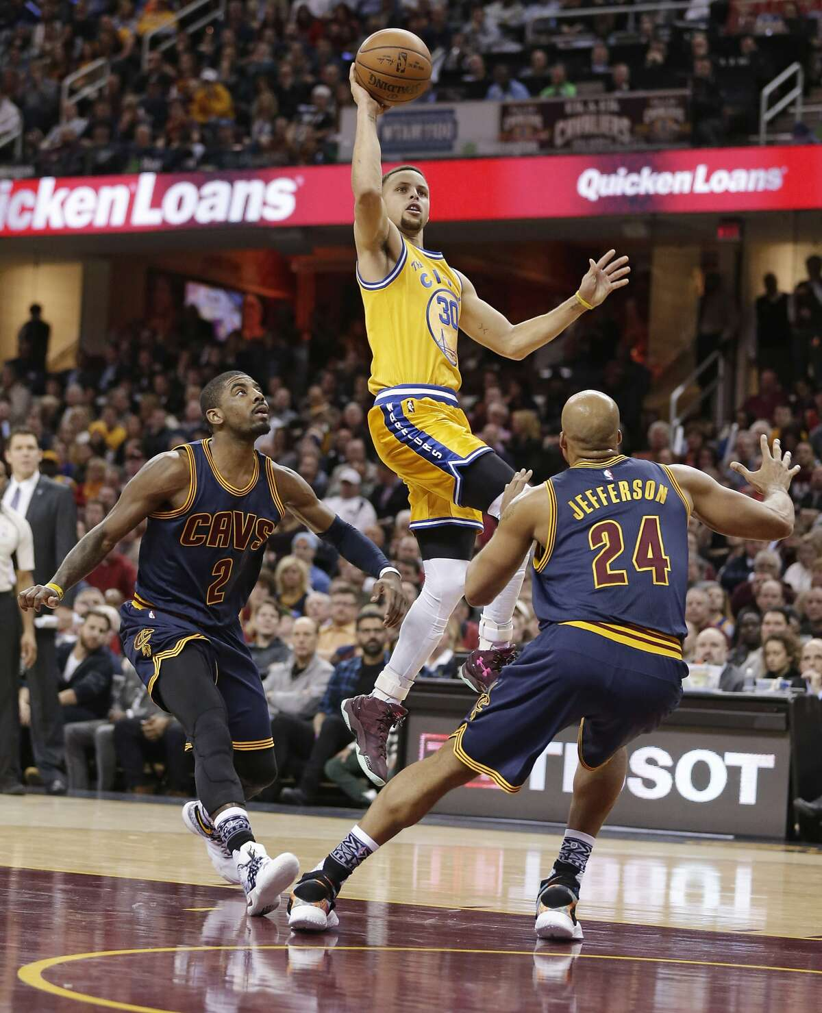 Golden State Warriors' Stephen Curry (30) shoots over Cleveland Cavaliers' Kyrie Irving (2) and Richard Jefferson (24) in the first half of an NBA basketball game Monday, Jan. 18, 2016, in Cleveland. (AP Photo/Tony Dejak)