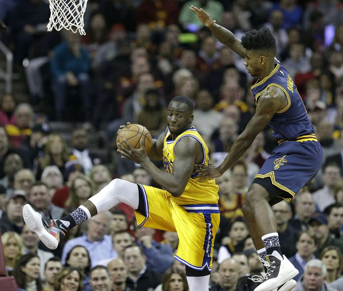 Golden State Warriors' Draymond Green, left, gets the rebound ahead of Cleveland Cavaliers' Iman Shumpert, right, in the first half of an NBA basketball game Monday, Jan. 18, 2016, in Cleveland. (AP Photo/Tony Dejak)