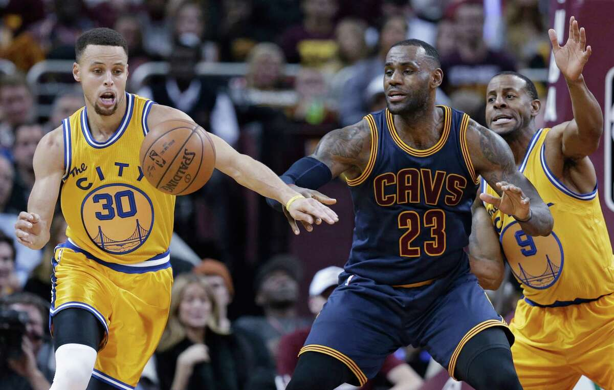 Golden State Warriors' Stephen Curry (30) knocks the ball loose from Cleveland Cavaliers' LeBron James (23) in the first half of an NBA basketball game, Monday, Jan. 18, 2016, in Cleveland. Andre Iguodala (9) is at right.