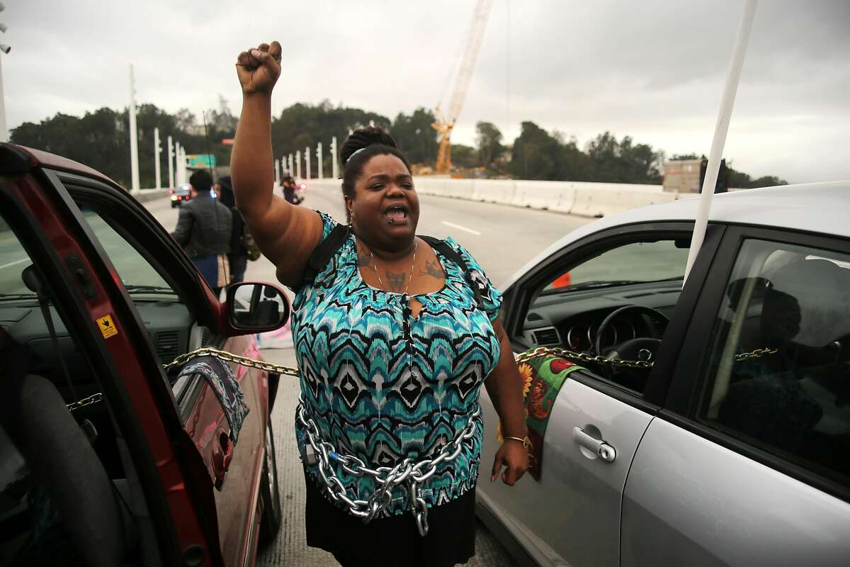 Vanessa Riles holds her fist up as she and other protestors block traffic during a demonstration against police brutality on the eastern span of the San Francisco-Oakland Bay Bridge in Oakland, California on January 18, 2016.