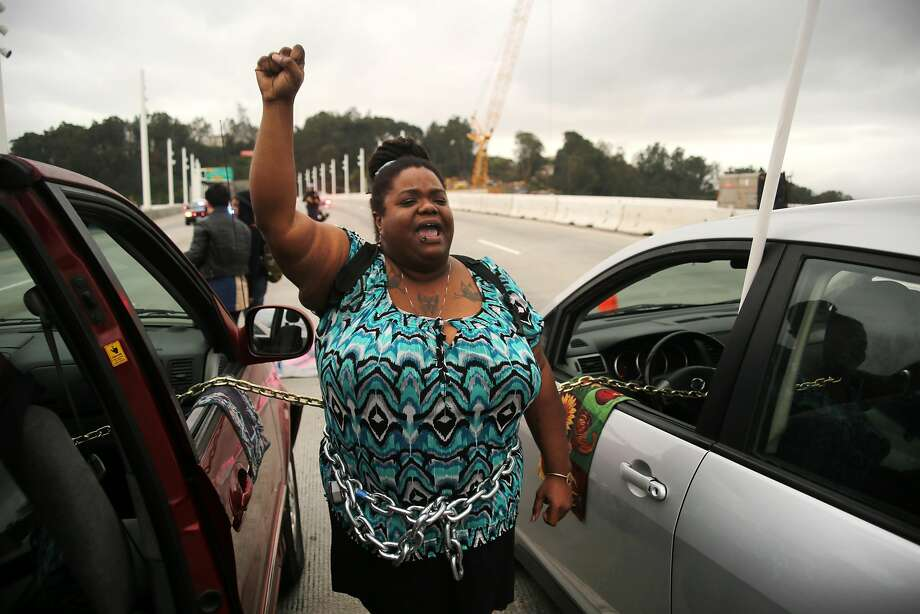 Vanessa Riles holds her fist up as she and other protestors block traffic during a demonstration against police brutality on the eastern span of the San Francisco-Oakland Bay Bridge in Oakland, California on January 18, 2016. Photo: Joel Angel Juárez