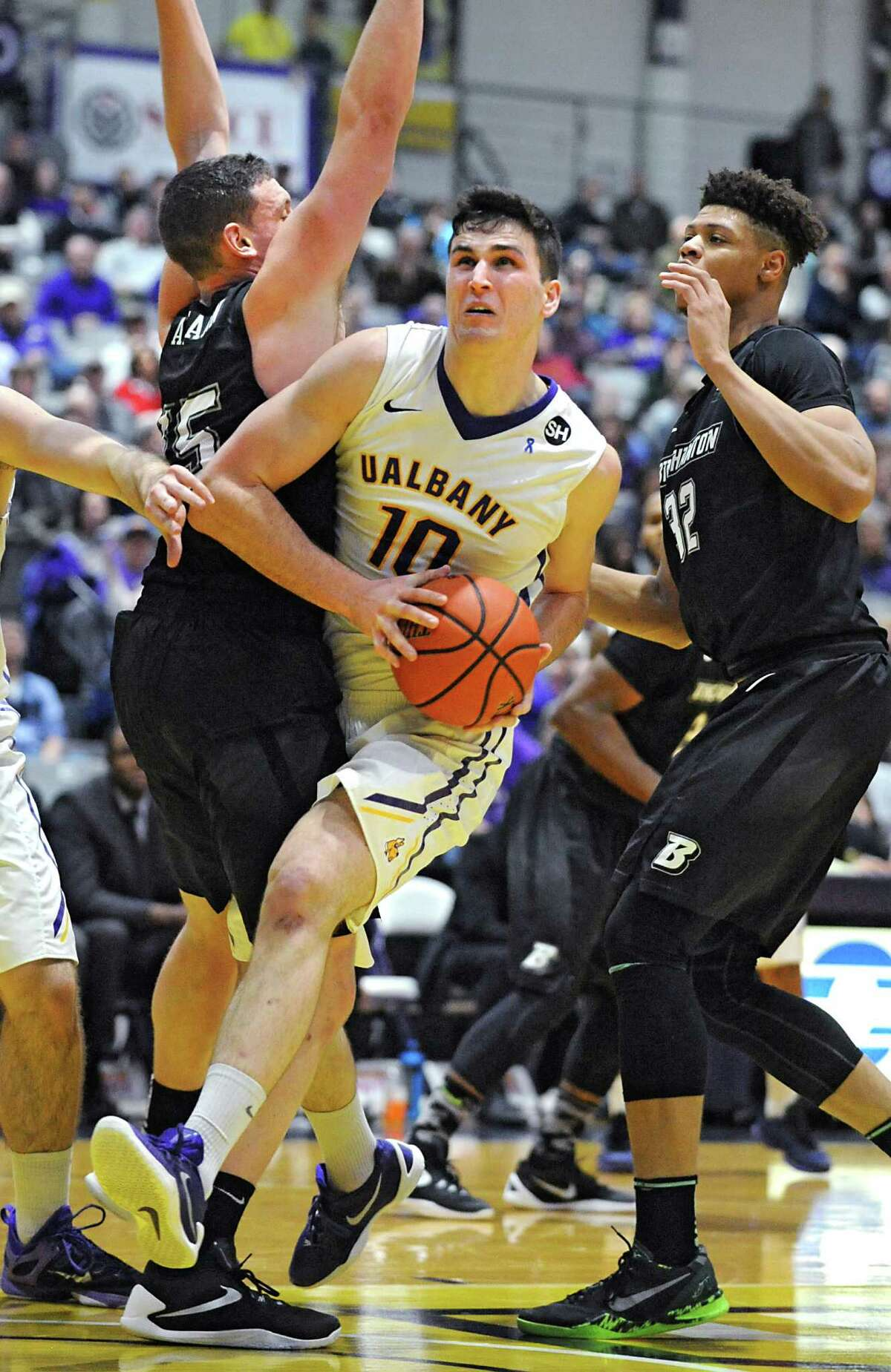 UAlbany's Mike Rowley drives to the basket defended by Binghamton's Bobby Ahearn, left, and Thomas Bruce during an America East Conference basketball game at the SEFCU Arena on Monday, Jan. 18, 2016 in Albany, N.Y. (Lori Van Buren / Times Union)