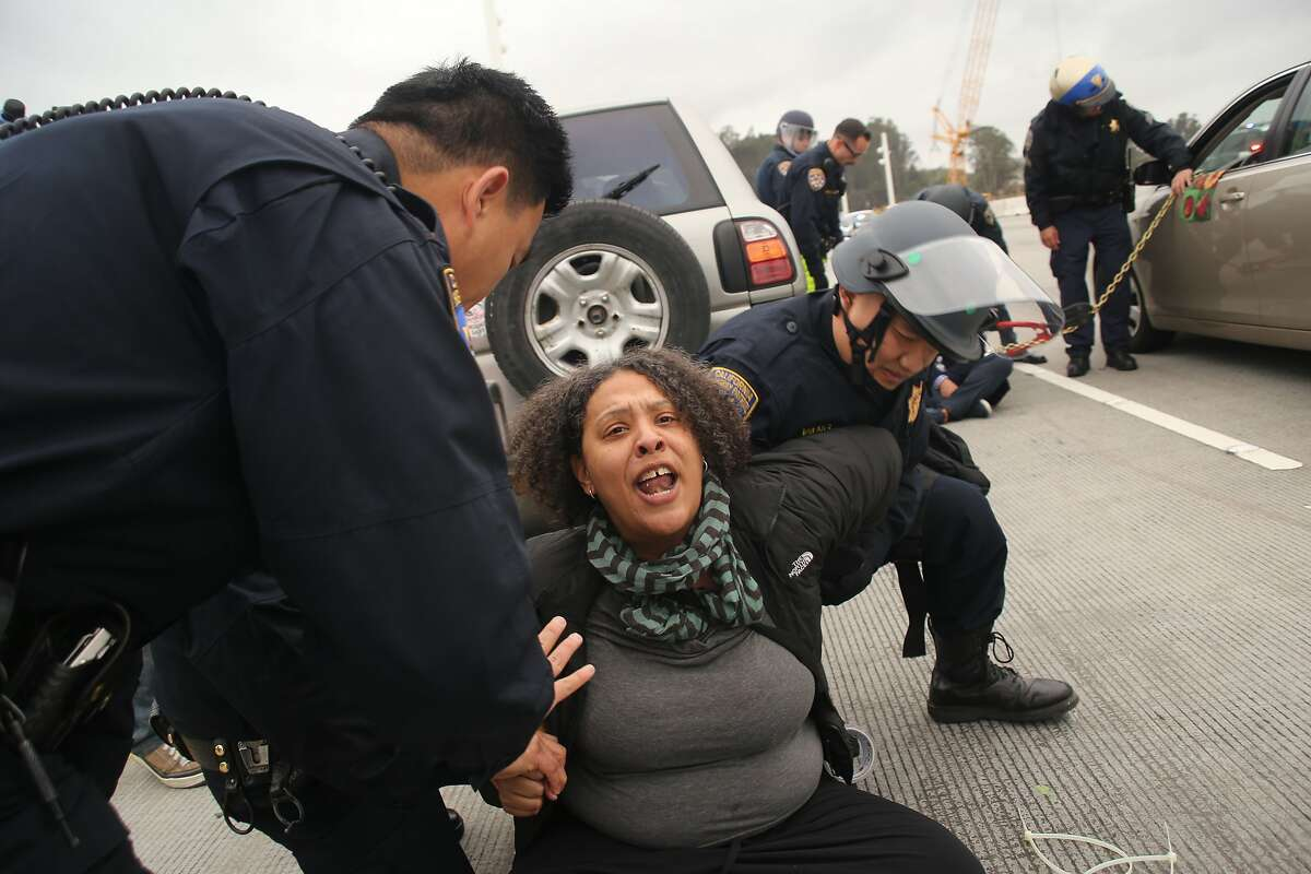Nanci Armstrong-Temple is arrested by CHP officers after blocking traffic during a demonstration against police brutality on the San Francisco-Oakland Bay Bridge in Oakland, California on January 18, 2016.