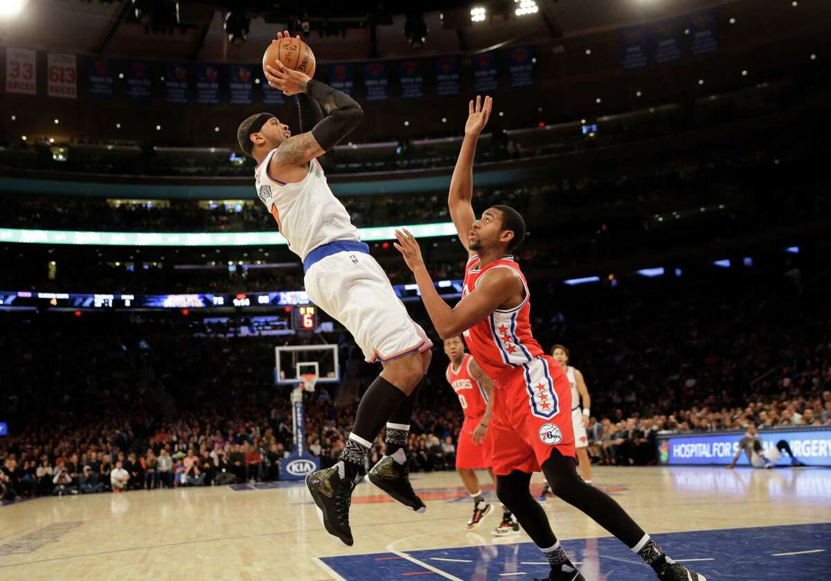 New York Knicks' Carmelo Anthony, left, puts up a shot over Philadelphia 76ers' Hollis Thompson during the second half of the NBA basketball game, Monday, Jan. 18, 2016 in New York. The Knicks defeated the 76ers in double overtime 119-113. (AP Photo/Seth Wenig) ORG XMIT: NYSW107