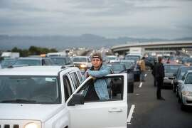 Motorists stand outside their vehicles as protesters block traffic on the San Francisco-Oakland Bay Bridge on Monday, Jan. 18, 2016, in San Francisco. A group of protesters from the group Black Lives Matter caused the shutdown of one side of the bridge in a police-brutality protest tied to the Rev. Martin Luther King Jr. holiday. (AP Photo/Noah Berger)