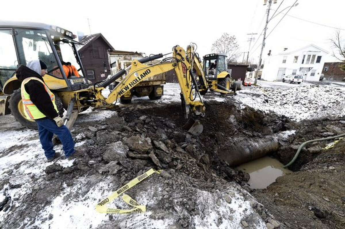A Troy highway worker gets started on repairs to the water main that ruptured over the weekend. (Skip Dickstein / Times Union)