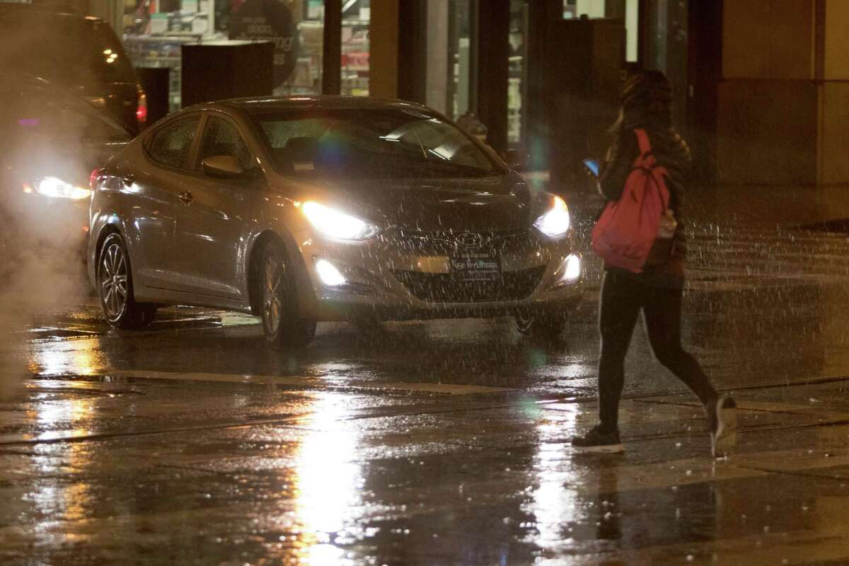 Pedestrians cover themselves during a rainfall in downtown San Francisco on Tuesday January 19, 2016.