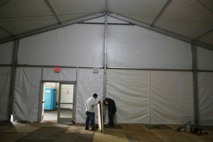 Nicolas Molina (l to r), laborer Avalon Tents, and Francisco Cifuentes, foreman Avalon Tents, work together as they set up a large tent for a temporary homeless shelter on Pier 80  on Friday, January 15, 2016 in San Francisco, Calif.