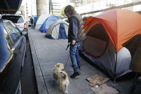 Chris (who declined to give her last name) walks past tents set up along 13th  Street as she walks her dog Taxie on Friday, January 15, 2016 in San Francisco, Calif.