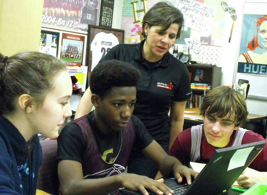 Ruth Wolf (standing), marketing manager for Sphier Emergency Room on South Mason Road, assists Cinco Ranch Junior High eighth-graders Sara Fuller, 14, left. Jelani Rowe, 13, and Hunter Hillegeist, 13, during a session of the school's writing project teaming students with local businesses.   Ruth Wolf (standing), marketing manager for Sphier Emergency Room on South Mason Road, assists Cinco Ranch Junior High eighth-graders Sara Fuller, 14, left. Jelani Rowe, 13, and Hunter Hillegeist, 13, during a session of the school's writing project teaming students with local businesses.