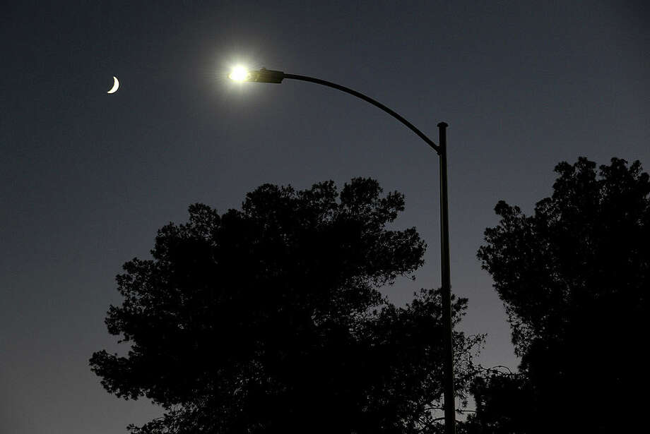 LAS VEGAS, NV - AUGUST 03:  A waxing crescent moon is seen behind a streetlight with a newly-installed LED fixture August 3, 2011 in Las Vegas, Nevada. The city is replacing 6,600 existing lights with the new energy-efficient LEDs, which are expected to reduce the city's annual electricity use by eight million kilowatt hours, saving about USD 400,000. The city estimates the LEDs will last about 15 years, nine years longer than the current lights. Funding for the project comes from federal energy conservation bonds and an American Recovery & Reinvestment Act grant. The city plans to replace all of its 50,000 streetlights after more funding is secured. Photo: Ethan Miller, Getty  / 2011 Getty Images