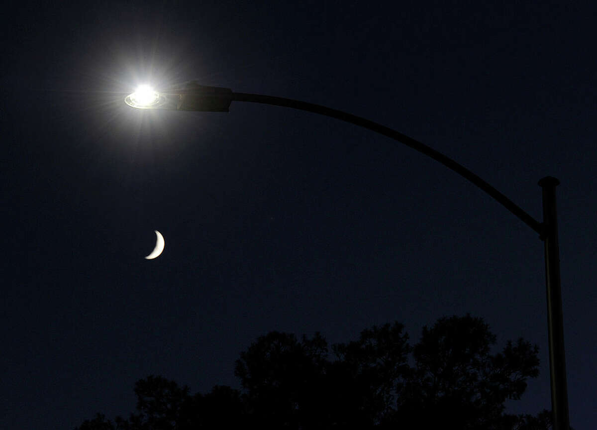 A waxing crescent moon is seen behind a streetlight with a newly-installed LED fixture August 3, 2011 in Las Vegas, Nevada. The city is replacing 6,600 existing lights with the new energy-efficient LEDs, which are expected to reduce the city's annual electricity use by eight million kilowatt hours, saving about USD 400,000. The city estimates the LEDs will last about 15 years, nine years longer than the current lights. Funding for the project comes from federal energy conservation bonds and an American Recovery & Reinvestment Act grant. The city plans to replace all of its 50,000 streetlights after more funding is secured.