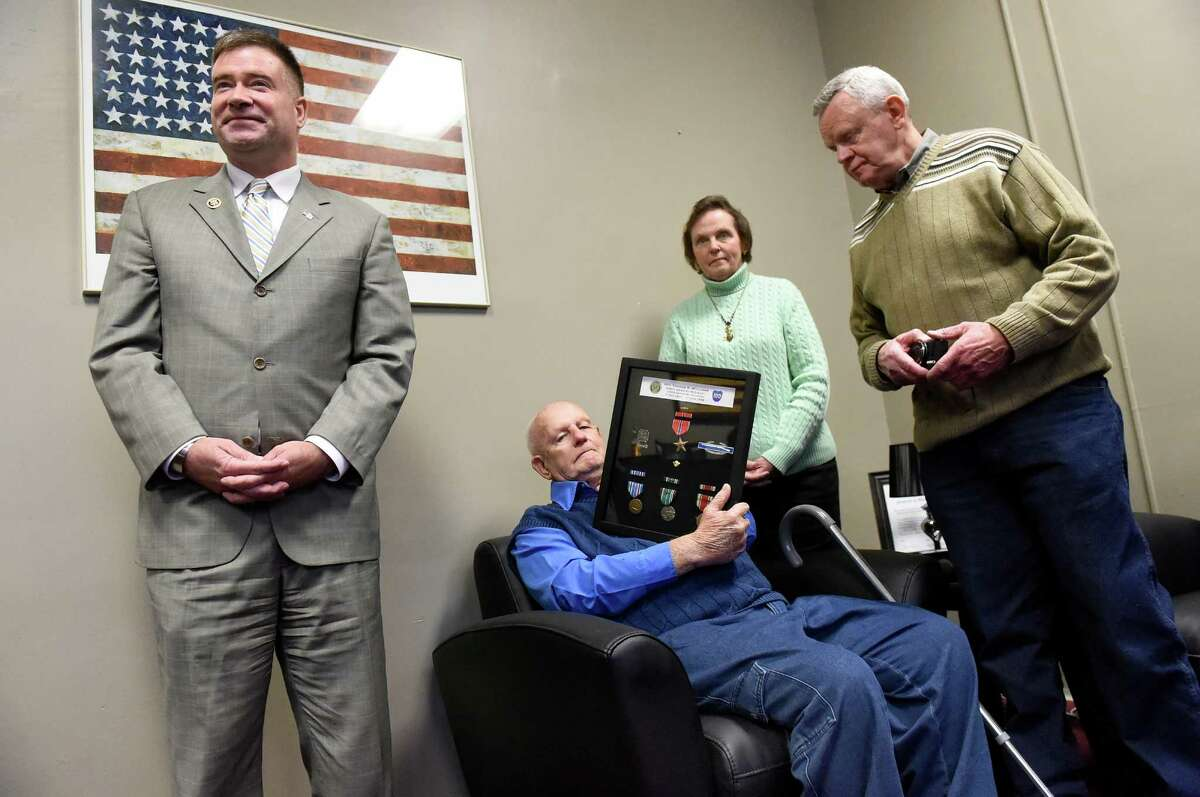 Thomas Williams, 92, of Central Bridge, center, holds World War II medals he received from Rep. Chris Gibson, left, during a ceremony on Tuesday, Jan. 19, 2016, at the Montgomery County Annex in Fonda, N.Y. Joining them are Williams' daughter Linda Engle and her husband David Engle. (Cindy Schultz / Times Union)