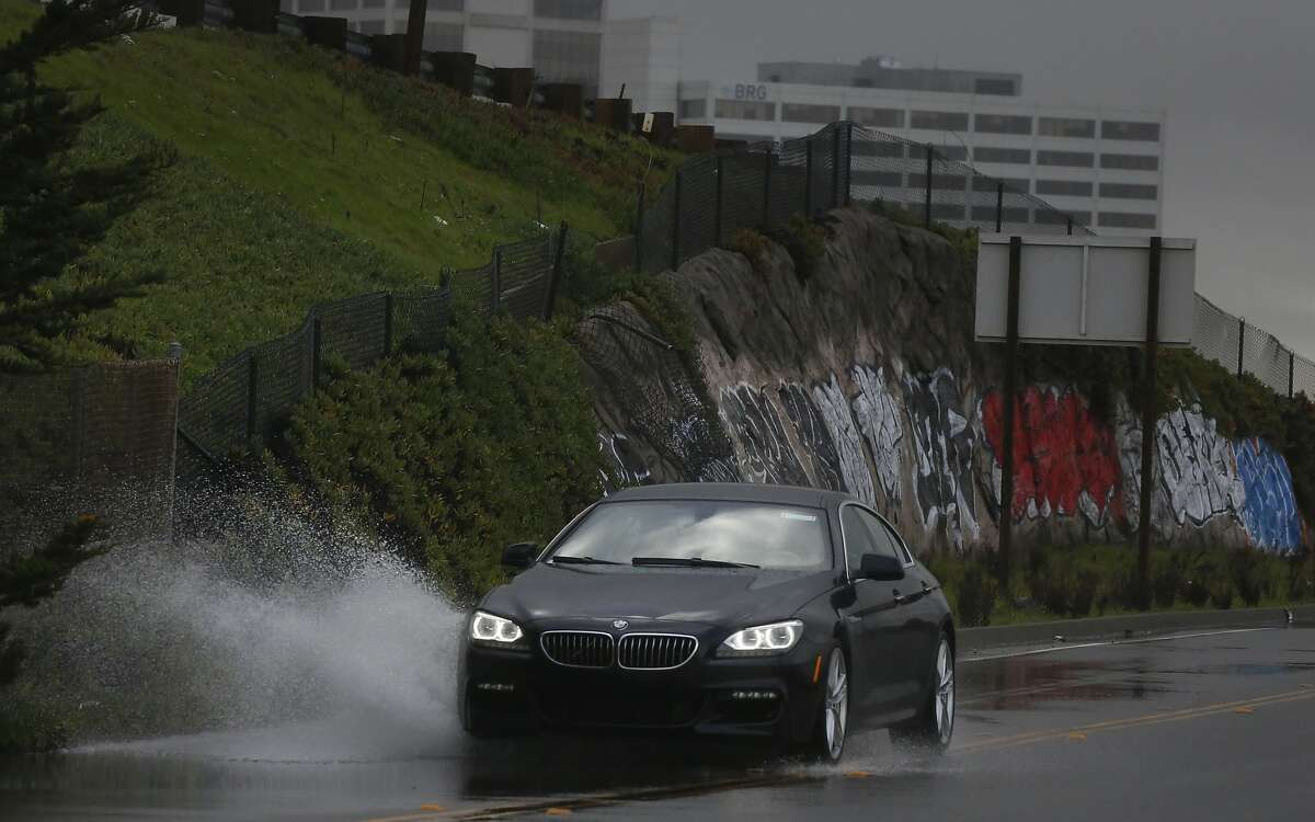 A car drives through a flooded area along W. Frontage Road Jan. 19, 2016 in Berkeley, Calif.