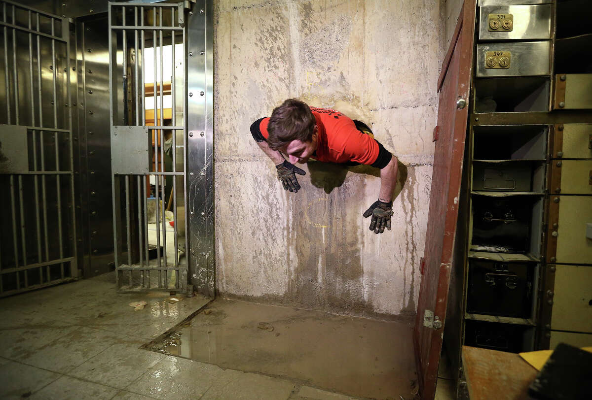 Diamond driller Sunny Kirby climbs through the hole used by burglars to access the underground vault of the Hatton Garden Safe Deposit Company which was raided in what has been called the largest burglary in English legal history on January 19, 2016 in London, England. Around 200 million GBP was stolen during the burglary which took place in April 2015. Four elderly men who were experienced thieves have since pled guilty to the crime while four other men are being tried on suspicion of involvement, one man, nicknamed 'Basil', is still at large.