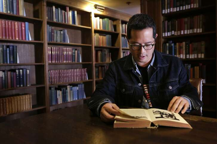 Jeff Chang leafs through a book in the Morrison Library on the U.C. Berkeley campus on Friday, October 17, 2014. The library was one of Chang's favorite hideaways while he was an undergraduate at the school. He was involved in activism and student government, and says his time at U.C. Berkeley helped spark his interest in politics and culture.