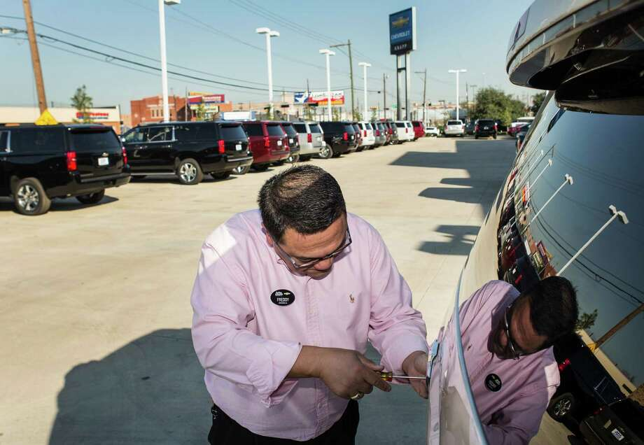 Salesman Freddy Barras puts a temporary tag on a new Chevrolet Tahoe for a customer at Knapp Chevrolet on Monday, Jan. 18, 2016, in Houston. Auto sales at the dealership was up 5.53 percent in 2015. ( Brett Coomer / Houston Chronicle ) Photo: Brett Coomer, Staff / © 2016 Houston Chronicle